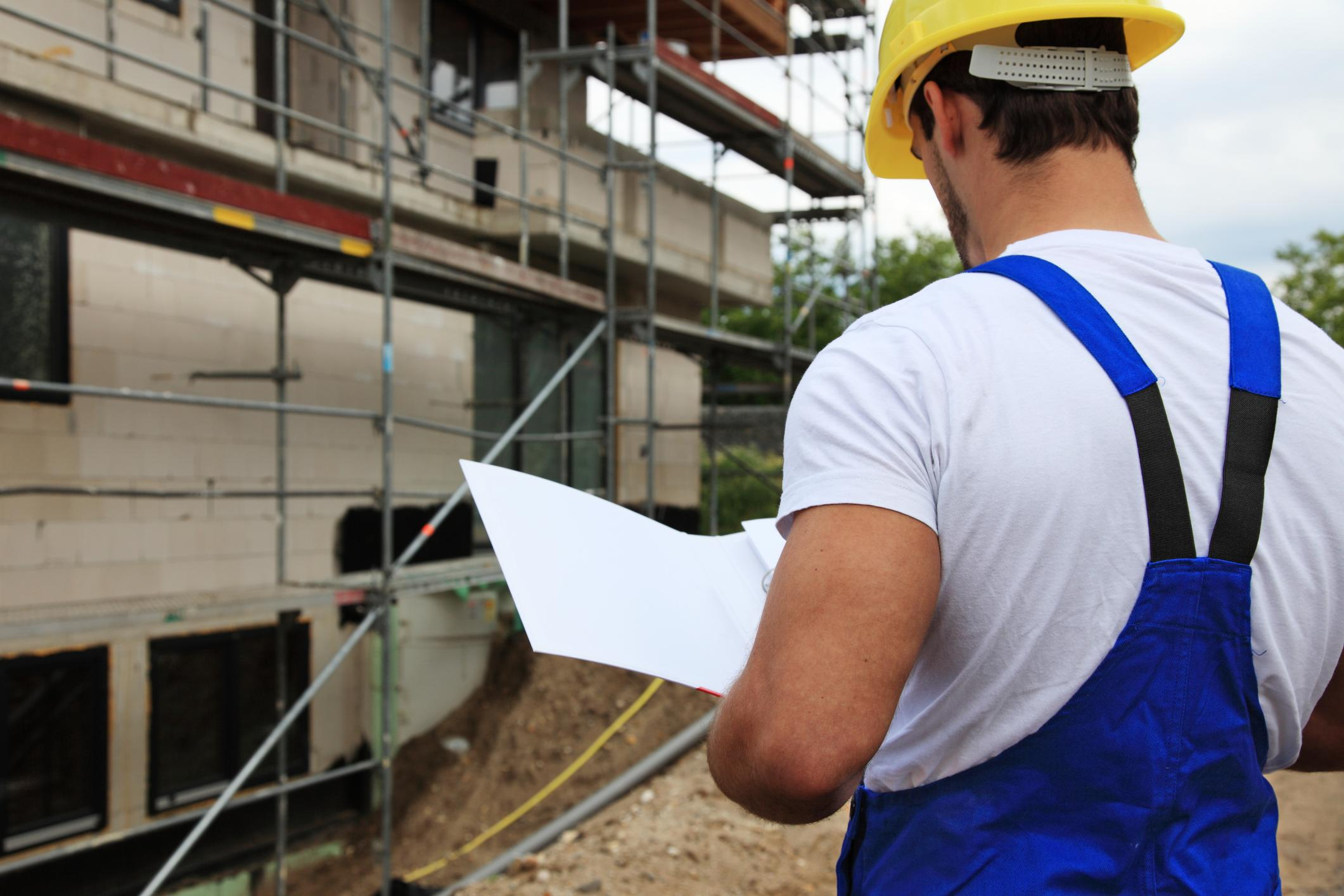 an architect beside an under construction house