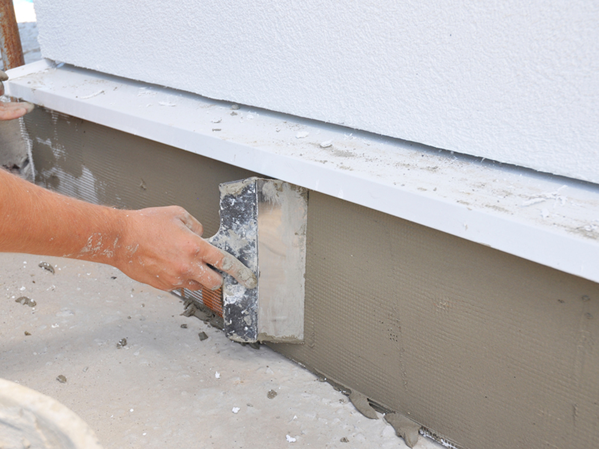 man smoothing out concrete wall